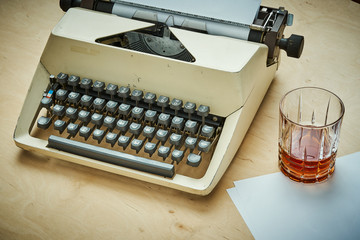 bright old typewriter with gray keys, paper and a glass of alcohol on a wooden table