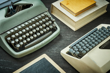 wo old typewriters and a book on a black wooden table