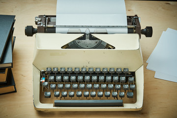bright old typewriter with gray keys and books on a wooden table