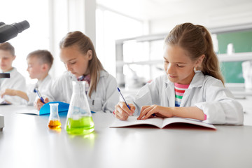 education, science and children concept - kids studying chemistry at school laboratory and writing...
