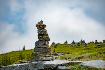 Stack of balancing stones on the top of a mountain in French Pyrenees with a view to downhills.