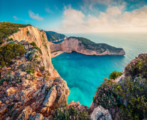 Colorful spring view of Navagio beach with shipwreck. Sunny morning seascape of Ionian Sea, Zakynthos (Zante) island, Greece, Europe. Beauty of nature concept background.