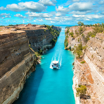 Beautiful scenery of the Corinth Canal in a bright sunny day against a blue sky with white clouds. Among the rocks floating white ship in turquoise water.
