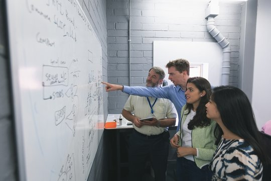Business people discussing over whiteboard