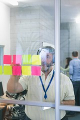 Male executive looking at sticky notes