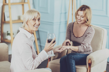 Alcoholic drink. Delighted aged woman drinking wine while sitting together with her daughter