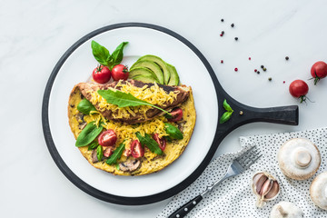 food composition with healthy omelette on wooden board and fork on white marble tabletop