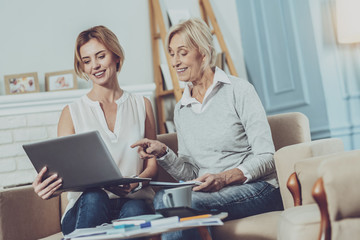 New ideas. Positive aged woman pointing at the laptop while discussing work together