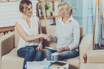Professional assistance. Positive aged woman sitting on the sofa while greeting her financial advisor