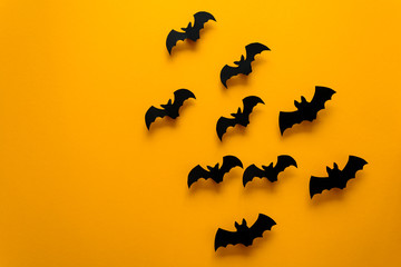Black paper bats flying on yellow background. Halloween concept. Paper cut style. Top view