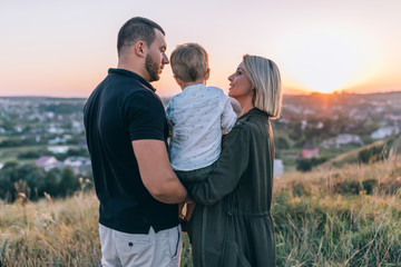 back view of happy parents carrying adorable little son at sunset