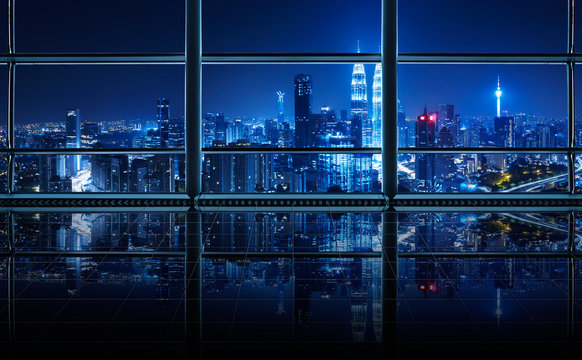 Modern empty and clean office interior with glass windows and city skyline background , night scene .