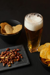 Light beer in a glass bowl on a black background.Beer in the bar and snacks, chips, nuts.
