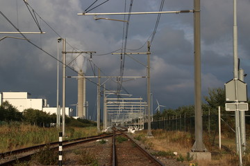Dark clouds above railroad track with a switch in the port of Amsterdam with chimney with steam in background.