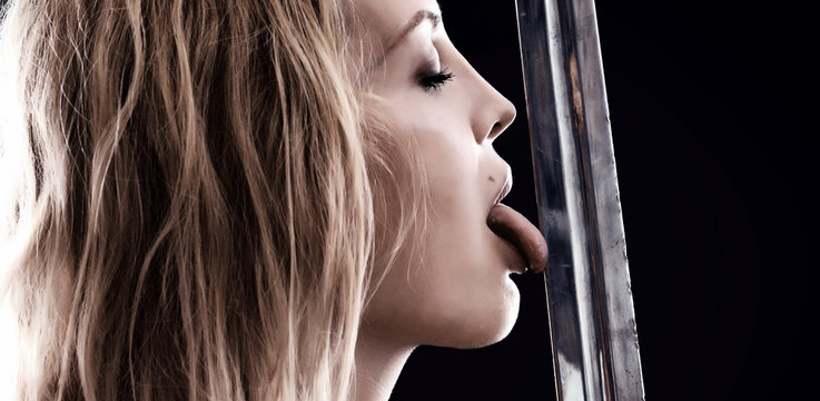 sexy warrior viking girl licks the blade of sword