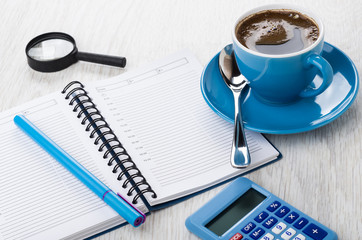 Calculator, notepad, pen, magnifying glass, coffee in blue cup