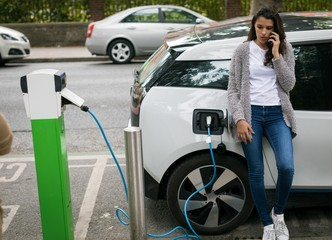 Woman talking on mobile phone while charging electric car