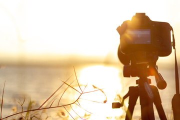 silhouette of camera on tripod shooting beautiful calm sea with sun on water at sunrise or sunset