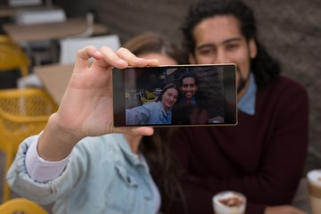 Couple taking selfie at outdoor cafe
