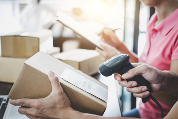 Home delivery service and working service mind, deliveryman working barcode scan checking order to confirm sending customer in post office
