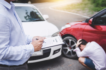 Traffic Accident and insurance concept, Insurance agent working on report form with car accident claim process