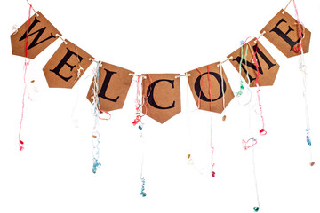 Welcome home party banner bunting with streamers against white background. The word welcome hanging on string.