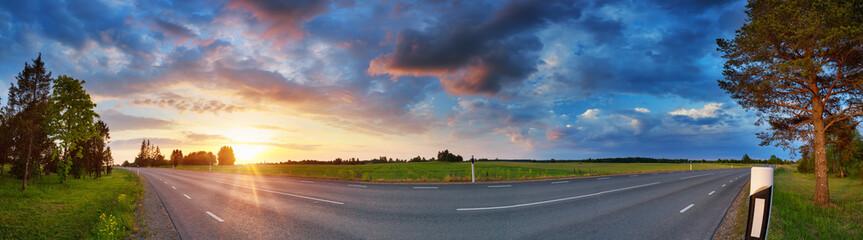 Wall Mural - black asphalt road and white dividing lines at sunset