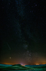 Milky way, Mars and Perseids meteor shower in clear night sky in front of green hill and field near small village in Russia