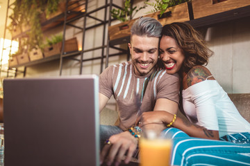 Young interracial couple spending time in cafe watching media together on laptop.