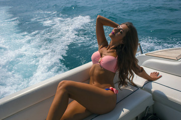 Young beautiful brunette girl sitting on the luxury yacht in a bathing suit. Girls sunbathing. Girl with long hair enjoying a cruise on a yacht.