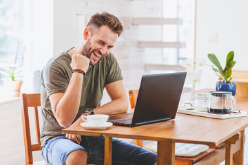 Young successful man working on laptop at home