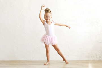 Little blonde balerina girl dancing and posing in dance club with wooden floot an white textured...