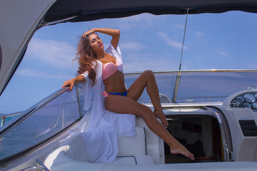 Portrait young beautiful brunette girl sitting on the luxury yacht in a bathing suit. Girls sunbathing. Girl with long hair enjoying a cruise on a yacht.