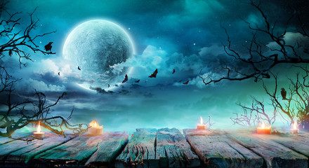 Halloween Background  - Old Table With Candles And Branches At Spooky Night With Full Moon