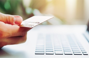 Man holding a credit card and typing. On-line shopping on the