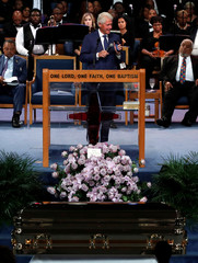 Former U.S. President Bill Clinton plays Aretha Franklin music on his mobile phone while speaking at the funeral service for the late singer at the Greater Grace Temple in Detroit