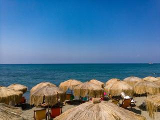 Viele Sonnenschirme aus Stroh am Strand mit Meer und blauen Himmel