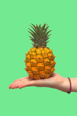 A pineapple in a hand of a young woman