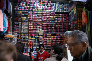 A woman sells cloth trimmings at a stand at Surco market in Lima