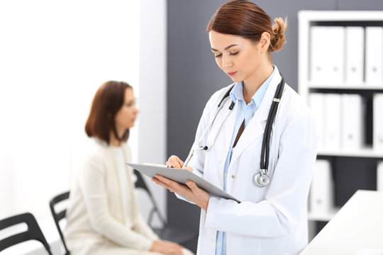 Doctor woman at work. Portrait of female physician filling up medical form while standing near reception desk at clinic or emergency hospital. Patient woman sitting at the background. Medicine concept
