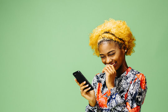 Young woman smiling and reacting to phone, isolated on green studio background