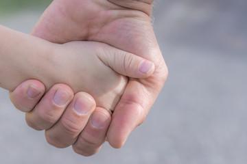 Vater hält Hand seines Kindes fest