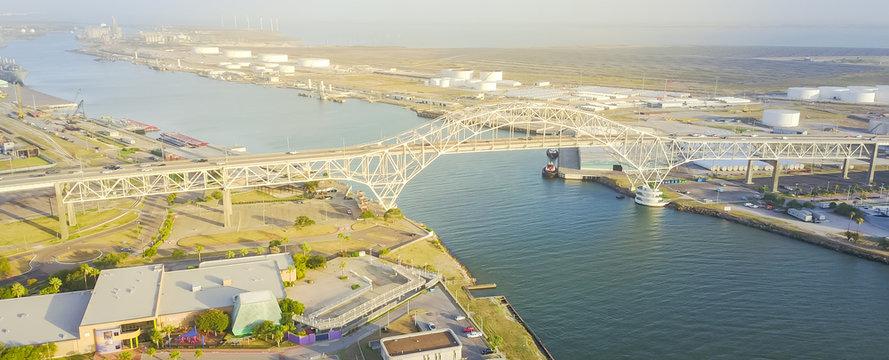 Panorama aerial view Harbor Bridge from Bayfront Science Park in Corpus Christi, Texas, US. Row of white oil tanks, wind turbines farm in distance. Industrial and transportation background