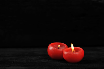 two red candles with lit fire on black background
