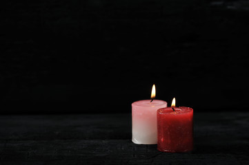 two candles with lit fire on black background