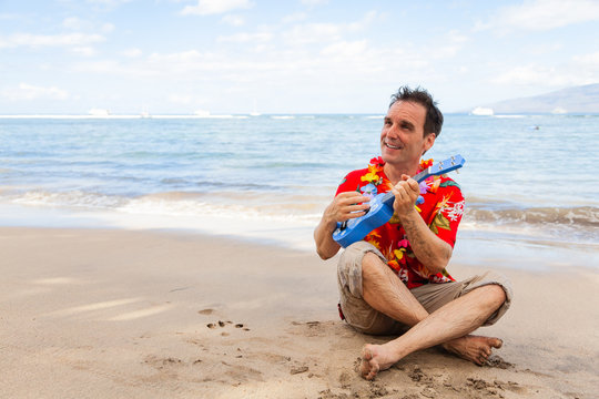 Happy Male Tourist Playing the Ukelele on the Beach with Copy Space