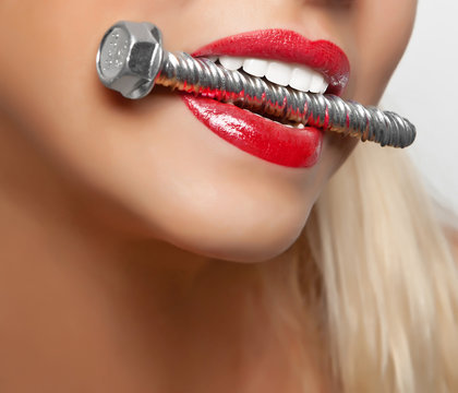 Big anchor bolt in the girl's teeth with red lipstick painted lips. Healthy strong teeth.