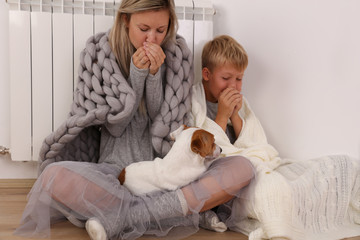 Cold home, freezing family, mother and son, Wrapped In Blanket Sitting Near Heater
