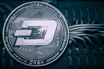 coin cryptocurrency Dash on the background of wires and circuits.