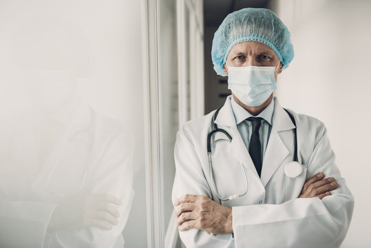 Serious Doctor in Mask and Cap with Crossed Arms